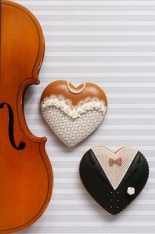 Violino velho e duas estatuetas da forma do coração do pão-de-espécie. noiva e noivo.