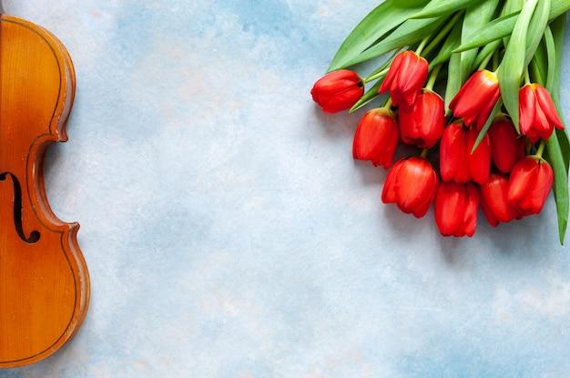 Violino velho e ramalhete de tulipas vermelhas.