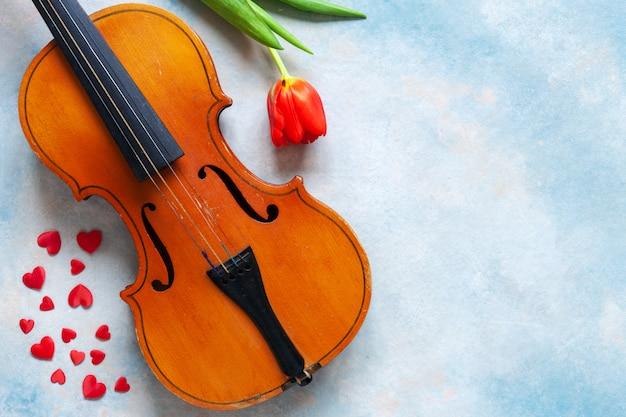 Violino velho, estatuetas vermelhas do coração e tulipa vermelha.