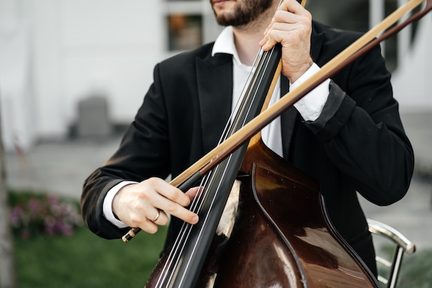 Violoncelista ou violoncelista no casamento. mãos masculinas em close-up de cordas de violoncelo.