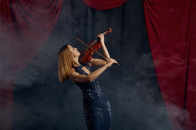 Violonista feminina com arco e violino, apresentação solo no palco. mulher com instrumento musical de cordas, arte musical, músico tocando viola
