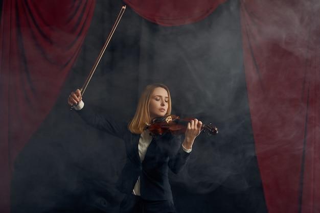 Violonista feminina com arco e violino, concerto solo no palco. mulher com instrumento musical de cordas, arte musical, músico tocando viola