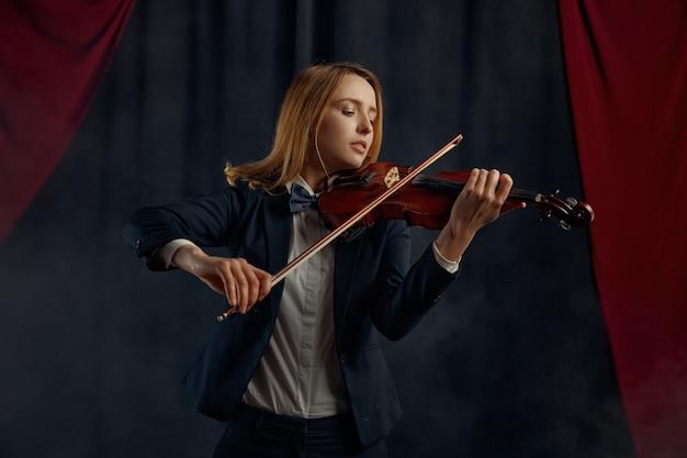Violonista feminina com arco e violino, concerto solo no palco. mulher com instrumento musical de cordas, músico toca viola