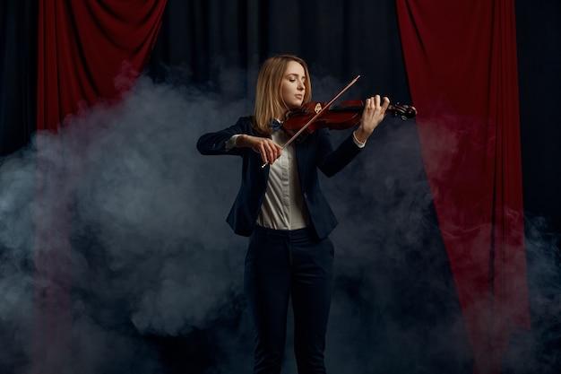 Violonista feminina com arco e violino, desempenho no palco. mulher com instrumento musical de cordas, arte musical, músico tocando viola