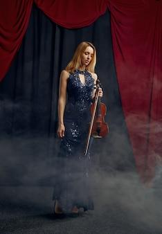 Violonista feminina detém violino em estilo retro. mulher com instrumento musical de cordas, arte musical, músico tocando viola