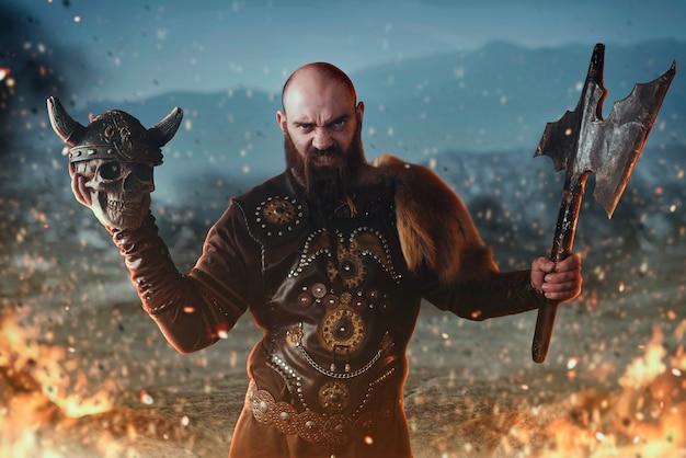 Viquingue zangado, vestido com roupas nórdicas tradicionais, segura o machado e o crânio humano, batalha no fogo. antigo guerreiro escandinavo