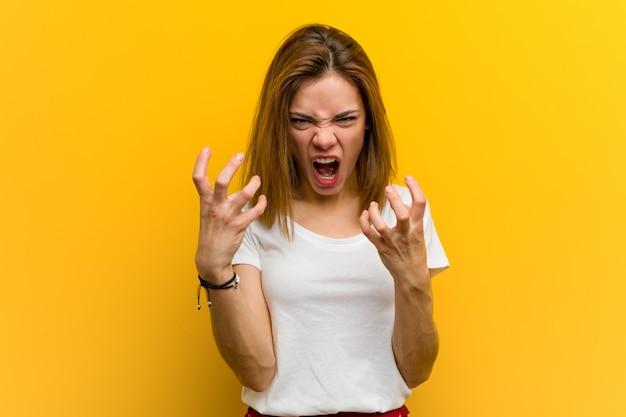 Virada natural caucasiano da mulher nova que grita com mãos tensas.