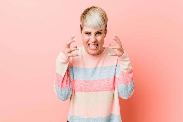 Virada natural curvilínea jovem mulher gritando com mãos tensas.