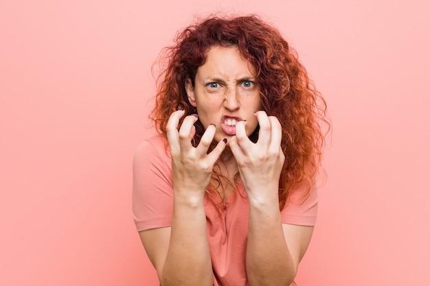 Virada natural e autêntica nova da ruiva mulher gritando com mãos tensas.