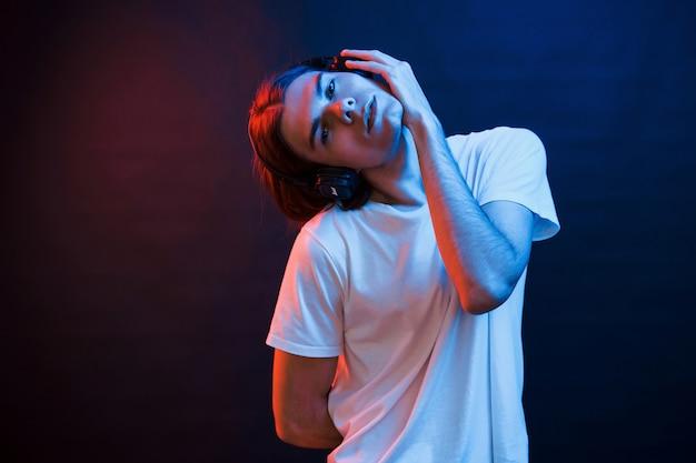 Virando a cabeça para o lado. estúdio filmado em estúdio escuro com luz de néon. retrato de homem sério