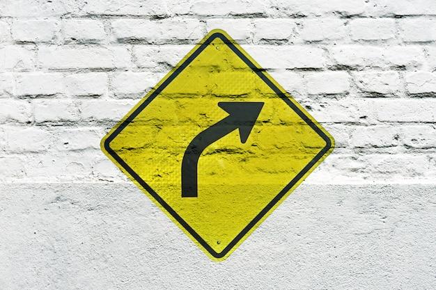 Vire à direita em frente: sinal de trânsito estampado na parede branca, como um grafite