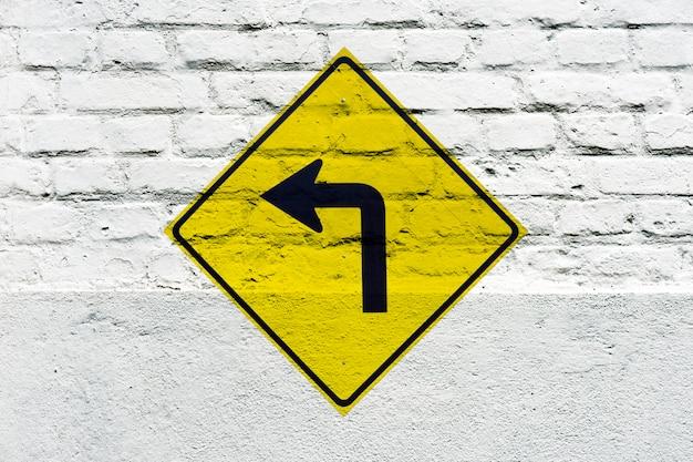 Vire à esquerda à frente: sinal de trânsito estampado na parede branca, como grafite