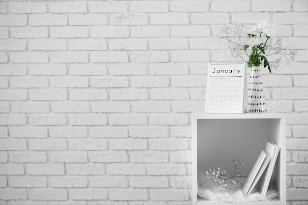 Vire o calendário e o vaso com buquê de flores na estante contra a parede de tijolos brancos