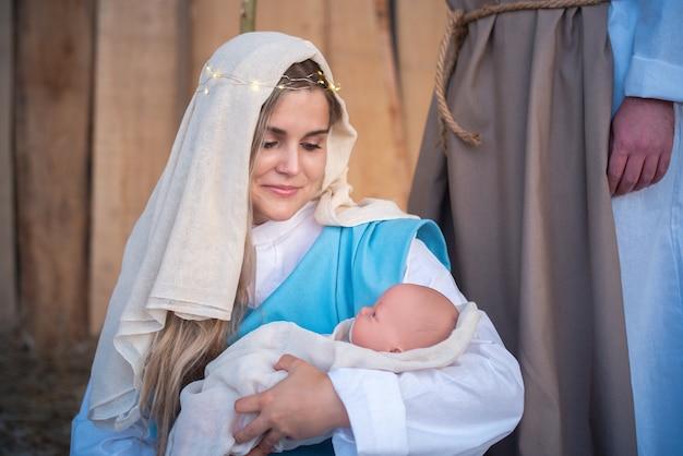 Virgem maria segurando o bebê de jesus em um presépio tradicional