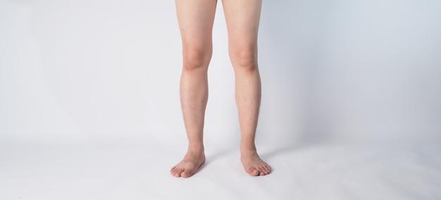 Virilha masculina asiática e perna e com os pés descalços no fundo branco.