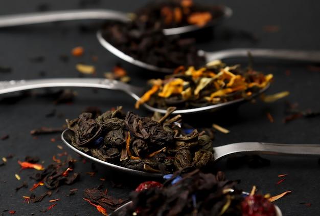 Virious tipos de chá em colheres de chá em close-up da mesa preta, variedade de chás. chá preto, verde e de frutas, folhas de chá secas.