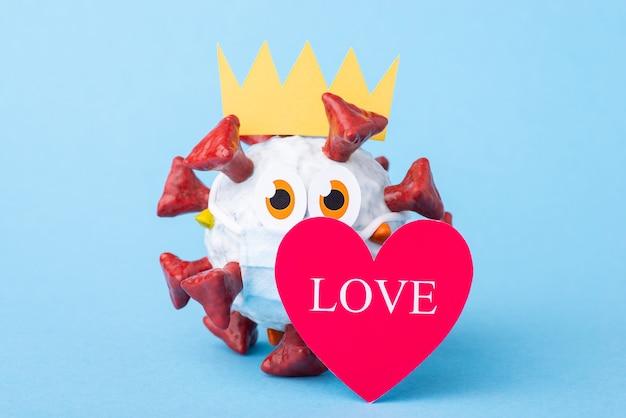 Vírus covid-19 bonito dos desenhos animados com um grande coração com a inscrição amor em um fundo azul