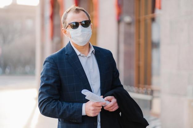 Vírus, pandemia, conceito de trabalho. gerente do sexo masculino usa terno formal e óculos de sol, máscara médica protetora para prevenir o coronavírus, mantém papéis nas mãos, posa ao ar livre perto do escritório, aguarda colega
