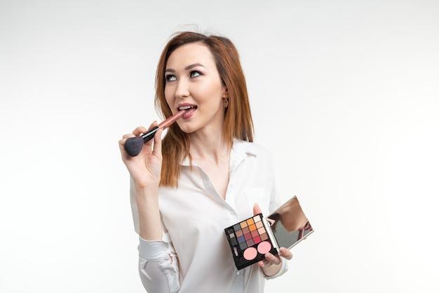 Visagista atraente ou maquiador coreano segurando pincéis de maquiagem e uma paleta de sombra para os olhos