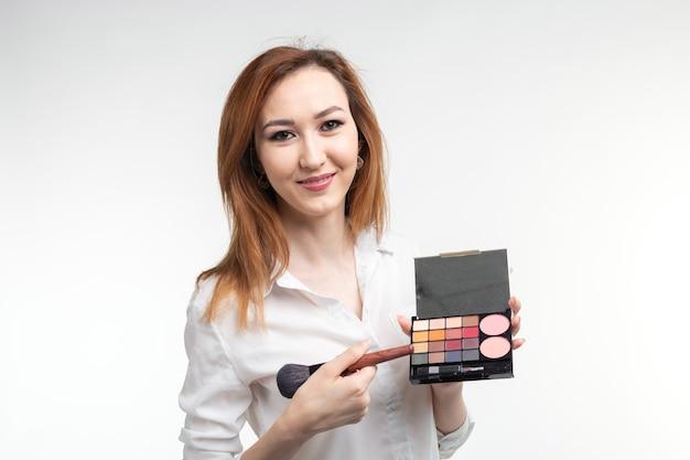 Visagista atraente ou maquiador coreano segurando um pincel de maquiagem e uma paleta de sombra no fundo branco