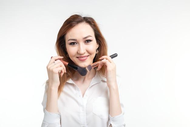 Visagista atraente ou maquiador coreano segurando um pincel de maquiagem