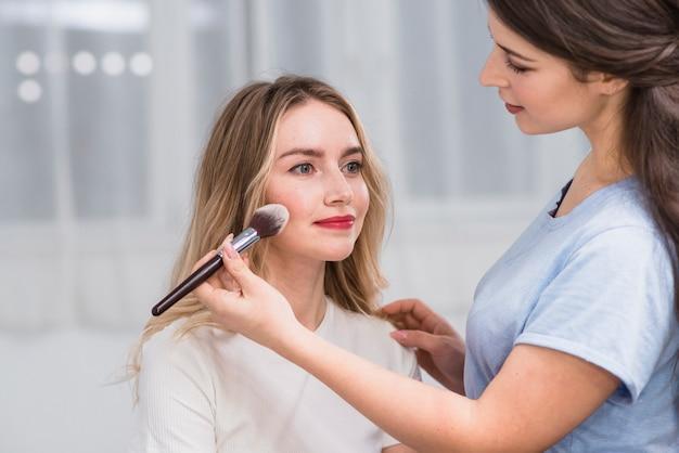 Visagiste feminina fazendo maquiagem para loira