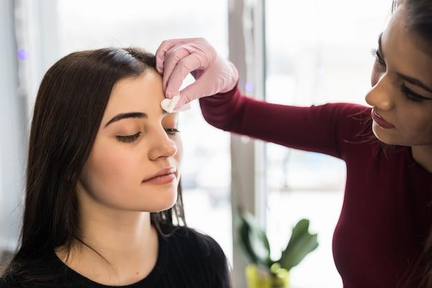 Visagiste hábil fazendo sobrancelhas negras maquiagem para uma jovem mulher