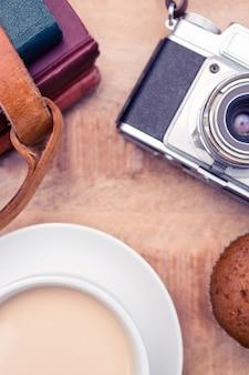 Visão aérea da câmera antiga com diários e café na mesa
