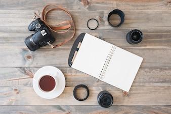 Visão aérea da câmera dslr; copo de chá; bloco de notas em espiral; caneta; lente de câmera e anéis de extensão em fundo de madeira