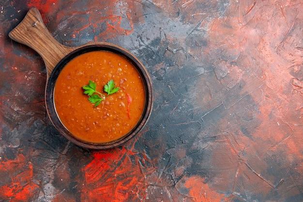 Visão aérea da clássica sopa de tomate em uma tábua de corte marrom em uma mesa de cores variadas