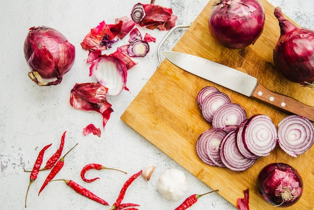 Visão aérea da faca; cebola cortada em cortar a placa com pimenta vermelha e alho