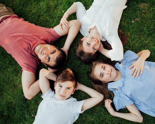 Visão aérea da família deitada na grama e olhando para a câmera