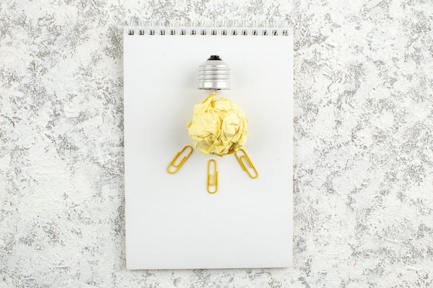 Visão aérea da lâmpada de papel no caderno espiral fechado branco na superfície branca