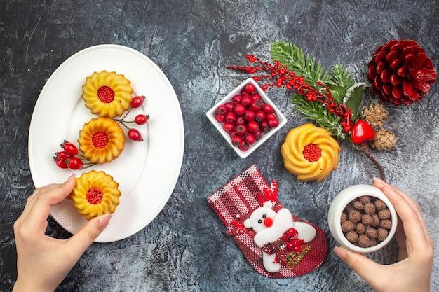 Visão aérea da mão pegando deliciosos biscoitos acessórios de decoração meias de papai noel e cornell em uma tigela ramos de abeto na superfície escura