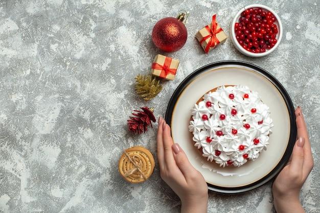 Visão aérea da mão segurando um bolo delicioso com groselha em um prato e caixas de presente empilhadas cones de coníferas de biscoitos em fundo cinza
