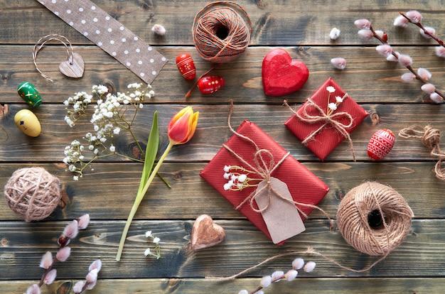 Visão aérea da mesa de madeira com decorações de primavera, presentes embrulhados, flores de salgueiro e tulipa e ovos de páscoa