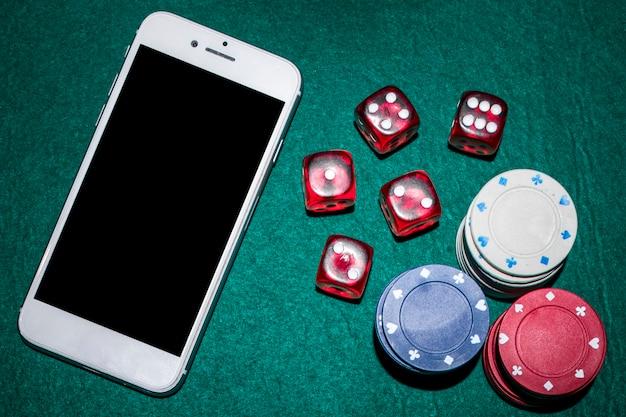 Visão aérea da mesa de poker com dadinhos vermelhos; fichas de casino e smartphone