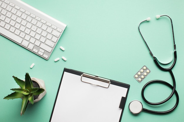 Visão aérea da mesa médica com planta suculenta e teclado sem fio na superfície verde