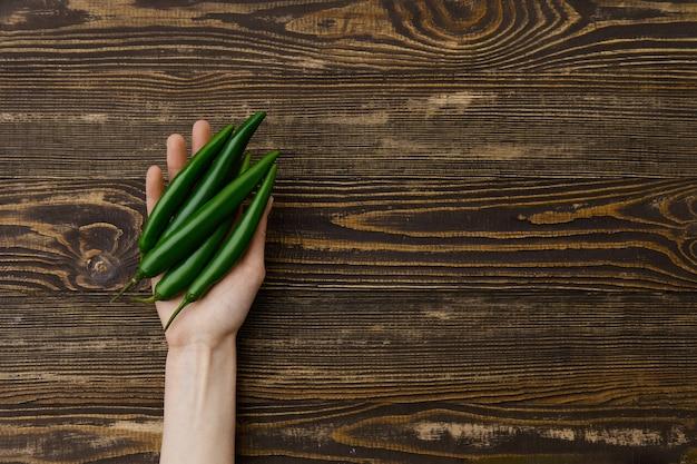Visão aérea da pimenta malagueta verde fresca nas mãos sobre o fundo de madeira