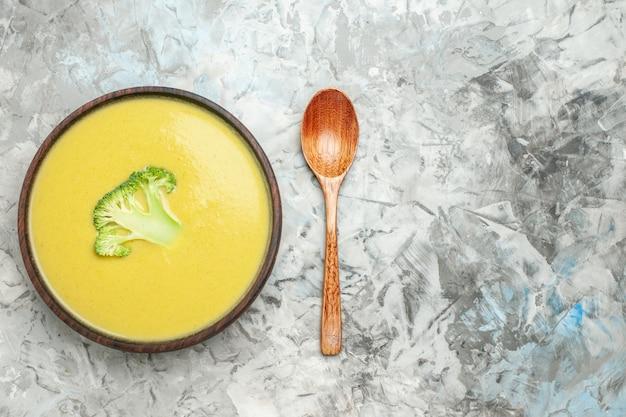 Visão aérea da sopa cremosa de brócolis em uma tigela marrom e colher na mesa cinza