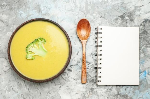 Visão aérea da sopa cremosa de brócolis em uma tigela marrom e uma colher ao lado do caderno na mesa cinza