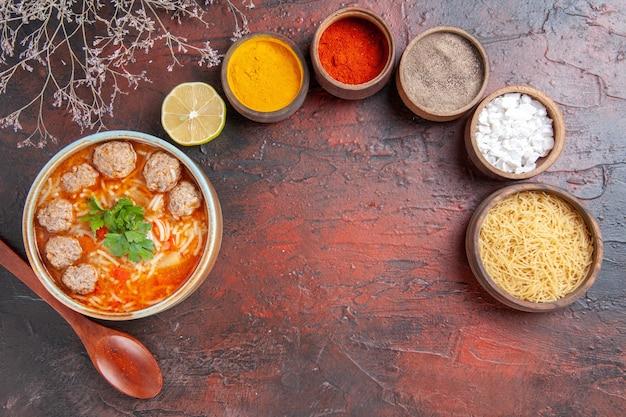 Visão aérea da sopa de almôndegas com macarrão em uma tigela marrom, colher de limão e macarrão cru e temperos diferentes na mesa escura