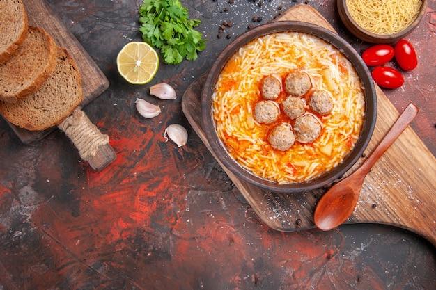Visão aérea da sopa de almôndegas com macarrão macarrão cru, tábua de cortar limão um monte de verdes tomates temperos diferentes na mesa escura