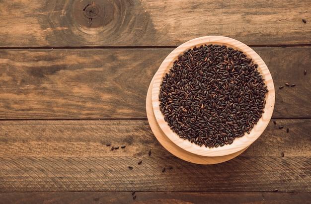 Visão aérea da tigela com grão de arroz preto sobre fundo de madeira