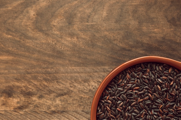 Visão aérea da tigela de arroz preto na mesa de madeira rústica