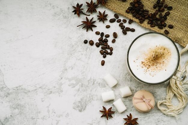 Visão aérea da xícara de café com anis estrelado; grãos de café; marshmallow e macaroon