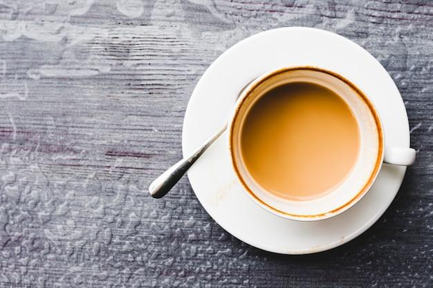 Visão aérea da xícara de café no pano de fundo de madeira molhada
