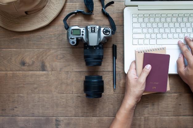 Visão aérea das mãos do homem usando o laptop e segurando o passaporte e a câmera no fundo de madeira