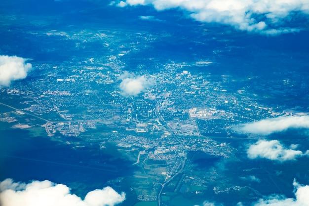 Visão aérea das nuvens brancas e da paisagem verde da vila