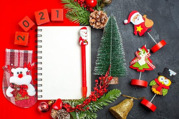 Visão aérea de acessórios de decoração de caderno espiral ramos de abeto xsmas números de meias em um guardanapo vermelho e árvore de natal em fundo escuro